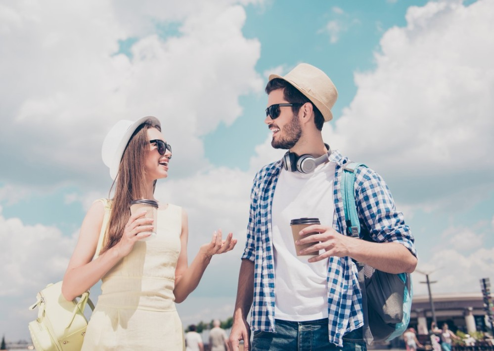 Bottom low angle view of cheerful positive stylish trendy couple in casual outfit with backpack walking in sunny day talking having hot beverage in hands, beautiful blue sky clouds background